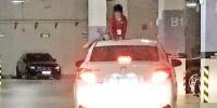 地下车库内,女孩坐在车顶上。 - 新浪