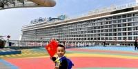 """4月15日,""""星梦邮轮""""旗下的""""世界梦号""""邮轮驶进厦门港。厦门国际邮轮母港集团负责人表示,迎来""""世界梦号"""",意味着厦门国际邮轮母港踏上""""大船时代""""的新起点。""""世界梦号""""邮轮是列入《2019伯利兹邮轮年鉴》的世界十大最佳大型邮轮之一,吨位15万,载客3376人,2017年底首航。图为小朋友在厦门国际邮轮母港观景平台玩耍。中新社记者 吕明 摄 - 福建新闻"""